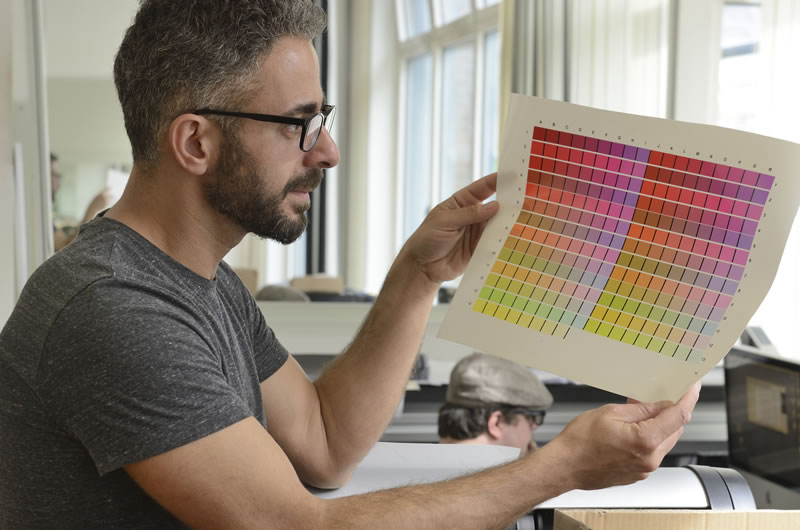 man in glasses holding up a print color chart