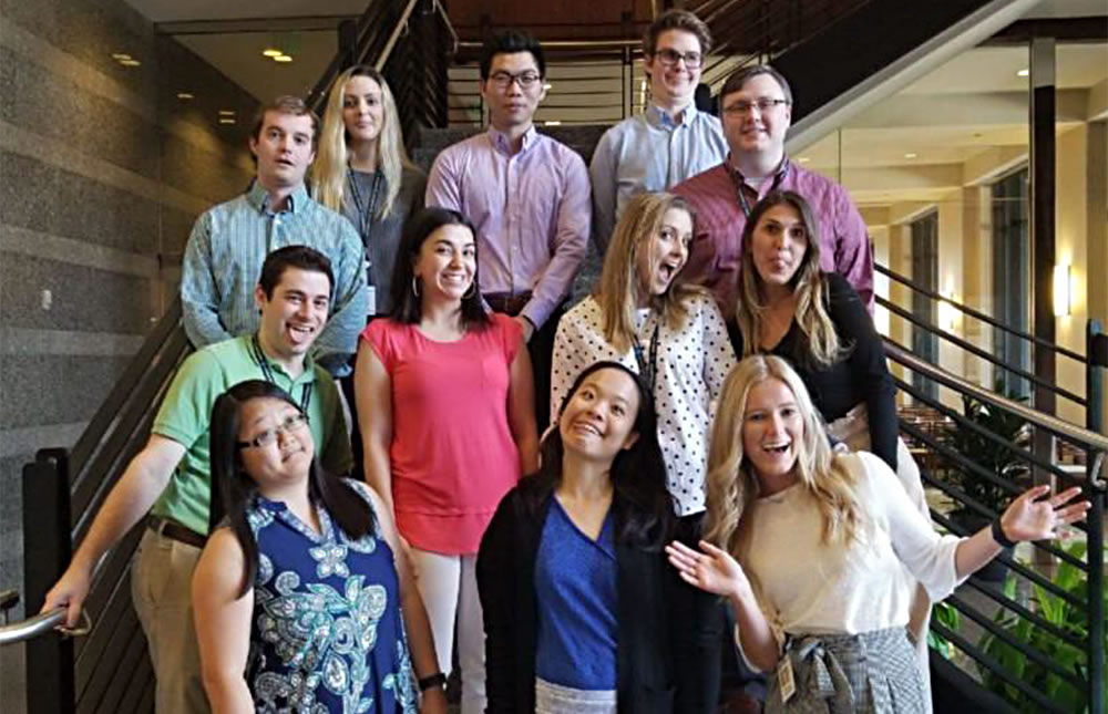 Printpack interns standing on a staircase.