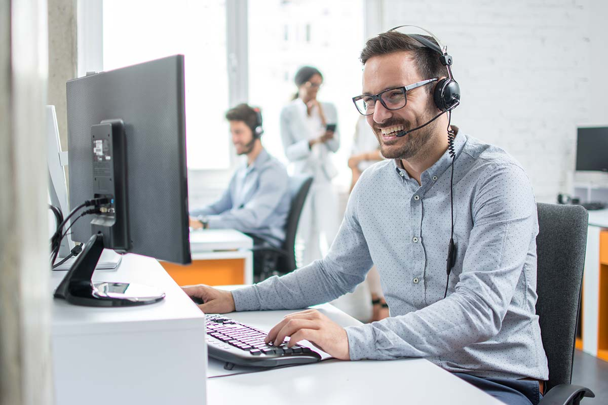 man with headset working on a computer