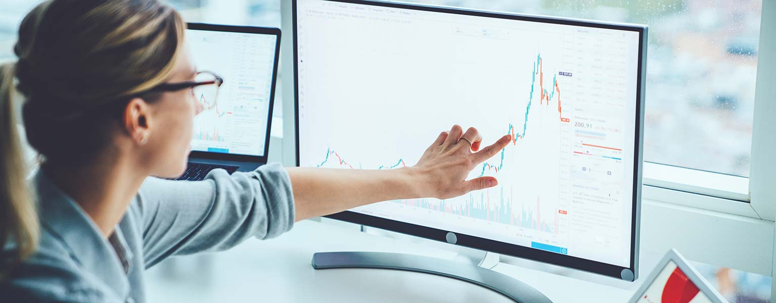 young woman pointing at monitor with sales graph on it